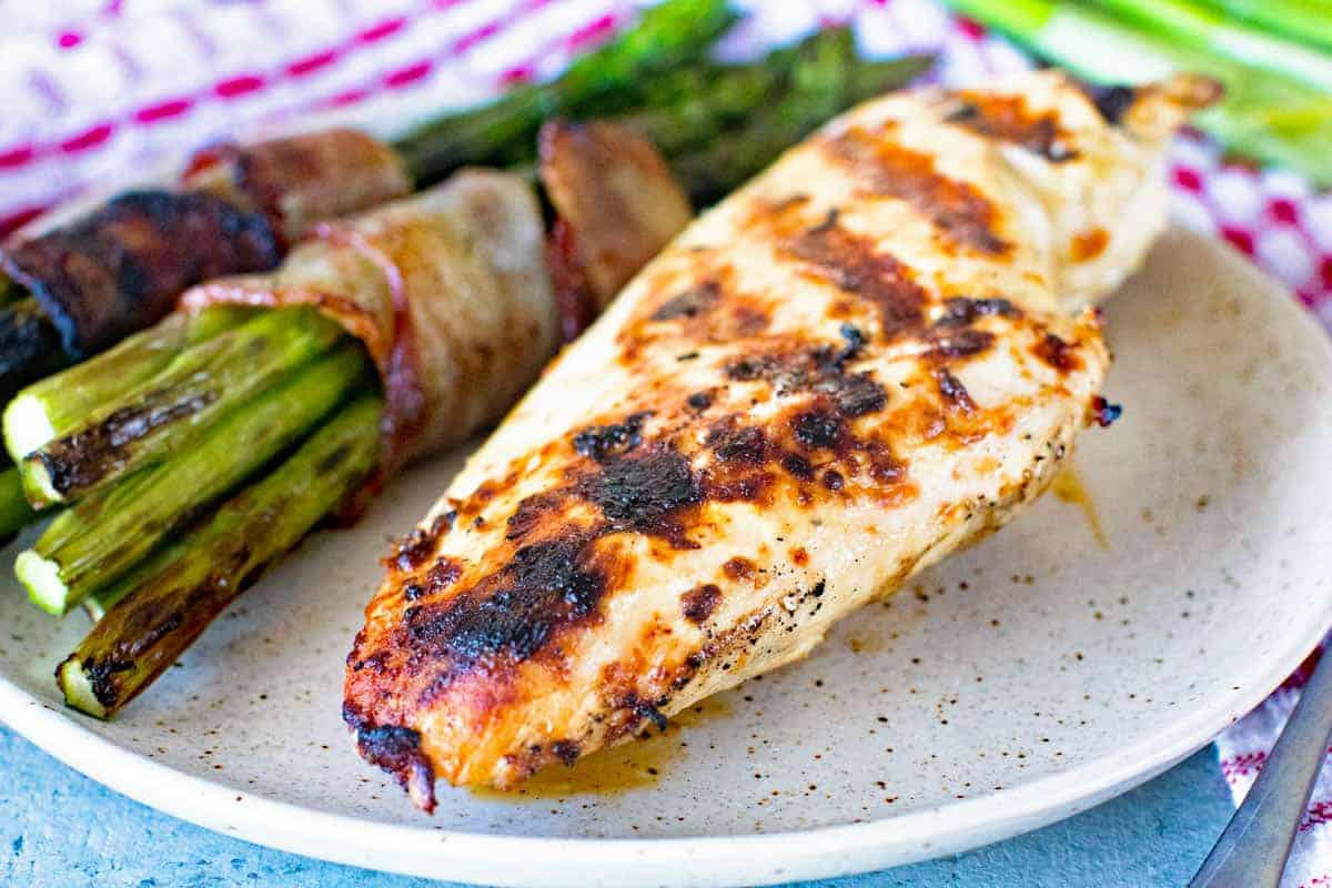 Caesar Grilled Chicken Breast and bacon wrapped asparagus on plate Landsacpe