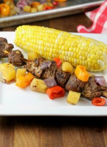 Balsamic pork skewers and corn on the cob on plate