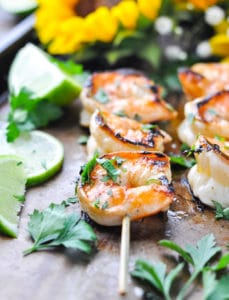 Marinated grilled shrimp and limes on baking sheet