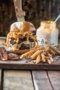 Spicy and smokey candied bacon burger and fries on cutting board