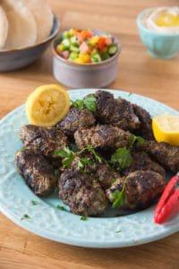 Beef kofta and lemons on plate