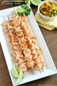 Grilled shrimp skewers and limes on plate