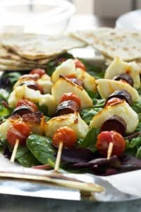Halloumi chorizo tomato skewers with spinach on a plate
