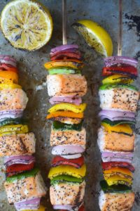 Rainbow salmon skewers and lemons on stone cutting board