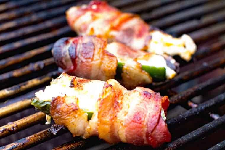 Grill rack with bacon wrapped jalapeno poppers on it