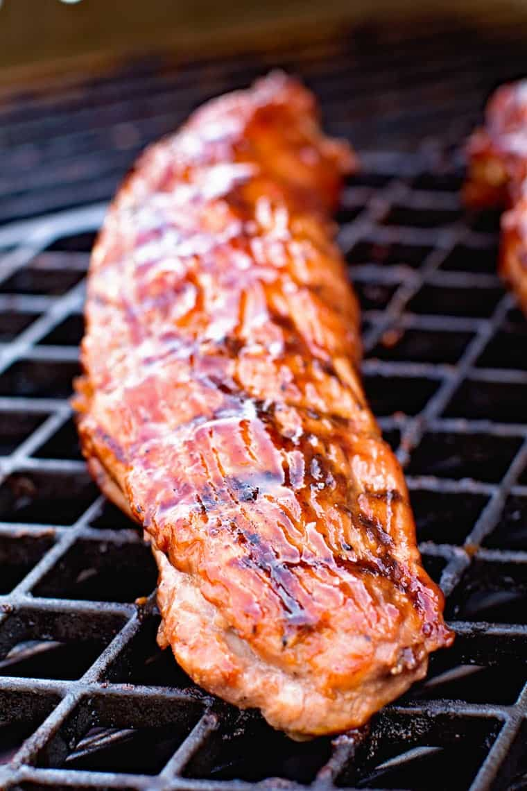 Grill grate with pork tenderloin that's been marinated in a bbq marinade and brushed with it.