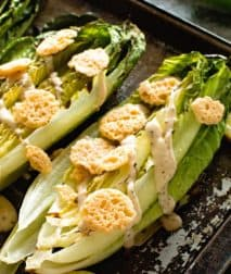 Grilled Caesar Salad with dressing on baking sheet