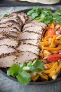 Grilled pork tenderloin fajitas and peppers on plate
