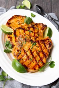 Thai curry grilled pork chops and limes on plate