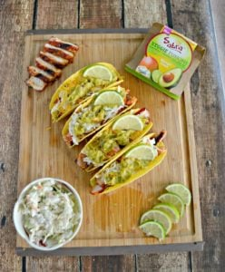 BBQ Pork tacos and surrounded by coleslaw, pork slices, lime slices, and guacamole package on a cutting board