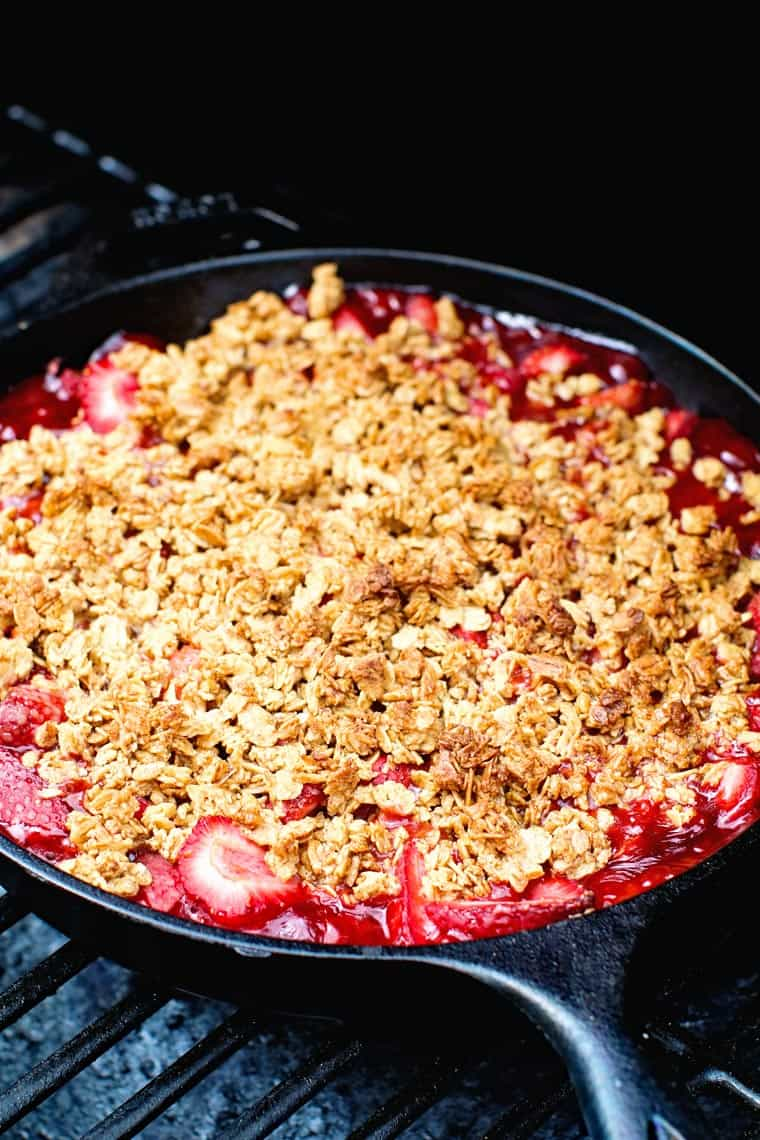 A cast iron skillet filled with on the grill. A strawberry crispy has been cooked until golden brown and delicious! #strawberrycrisp #strawberrycrumble #easydessert #grillingfavorites #gimmesomegrilling