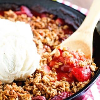 A black cast iron skillet filled with a hot bubbly strawberry crip. A wooden spoon is serving up a spoonful topped with vanilla ice cream.