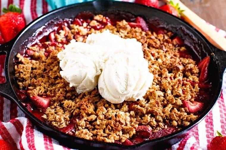 Hot and bubbly strawberry crisp made in the smoker. It's served with a dollop of vanilla ice cream.