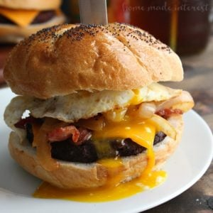 Bacon bbq meatloaf burger with a fried egg on top with a knife through the center