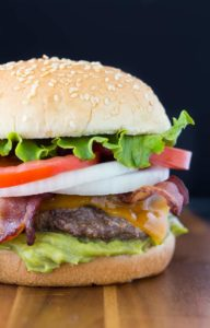 Cheese stuffed jalapeno burger with tomato, onion, bacon, and lettuce on wood table