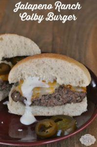 Jalapeno ranch colby burger cut in half and served with jalapeno slices on a plate
