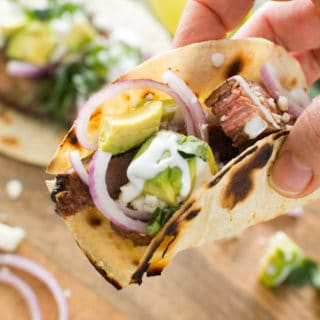 Hand holding chile lime steak taco