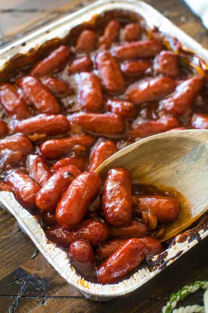 A pan of little smokies in bbq sauce with wooden spoon