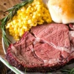 Smoked Prime Rib slice on plate with corn and dinner roll