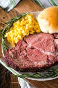 Smoked Prime Rib with corn and a dinner bun on a plate