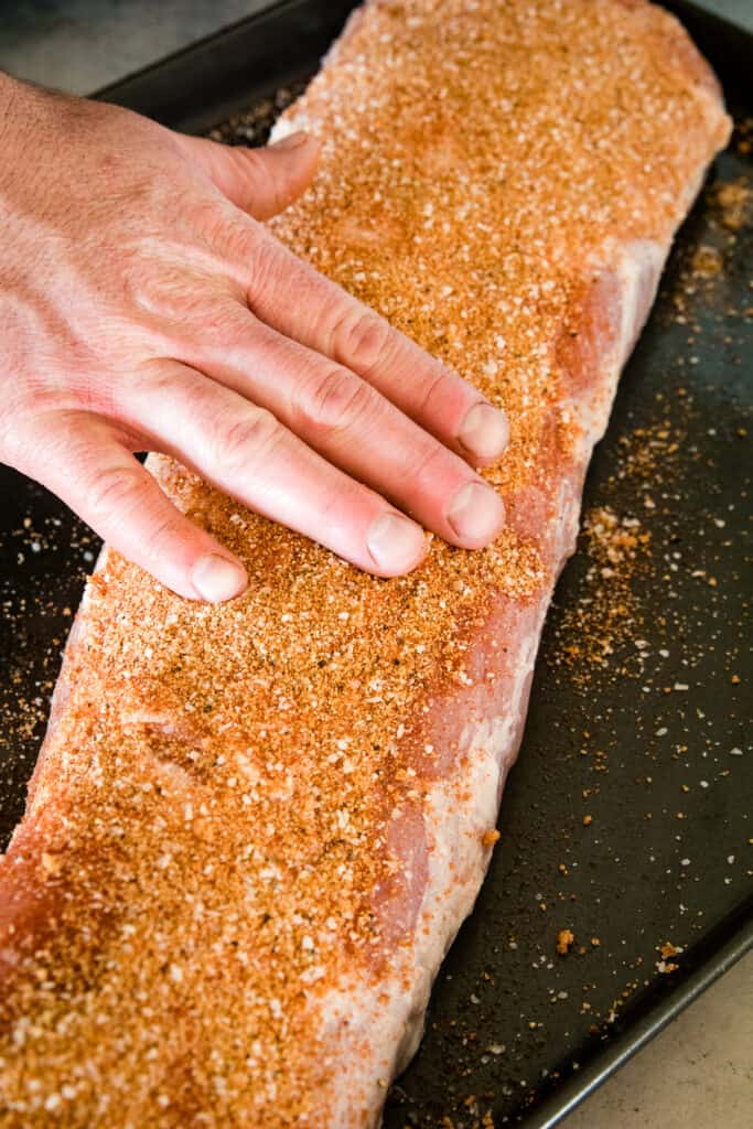 Hand rubbing dry rub on pork loin
