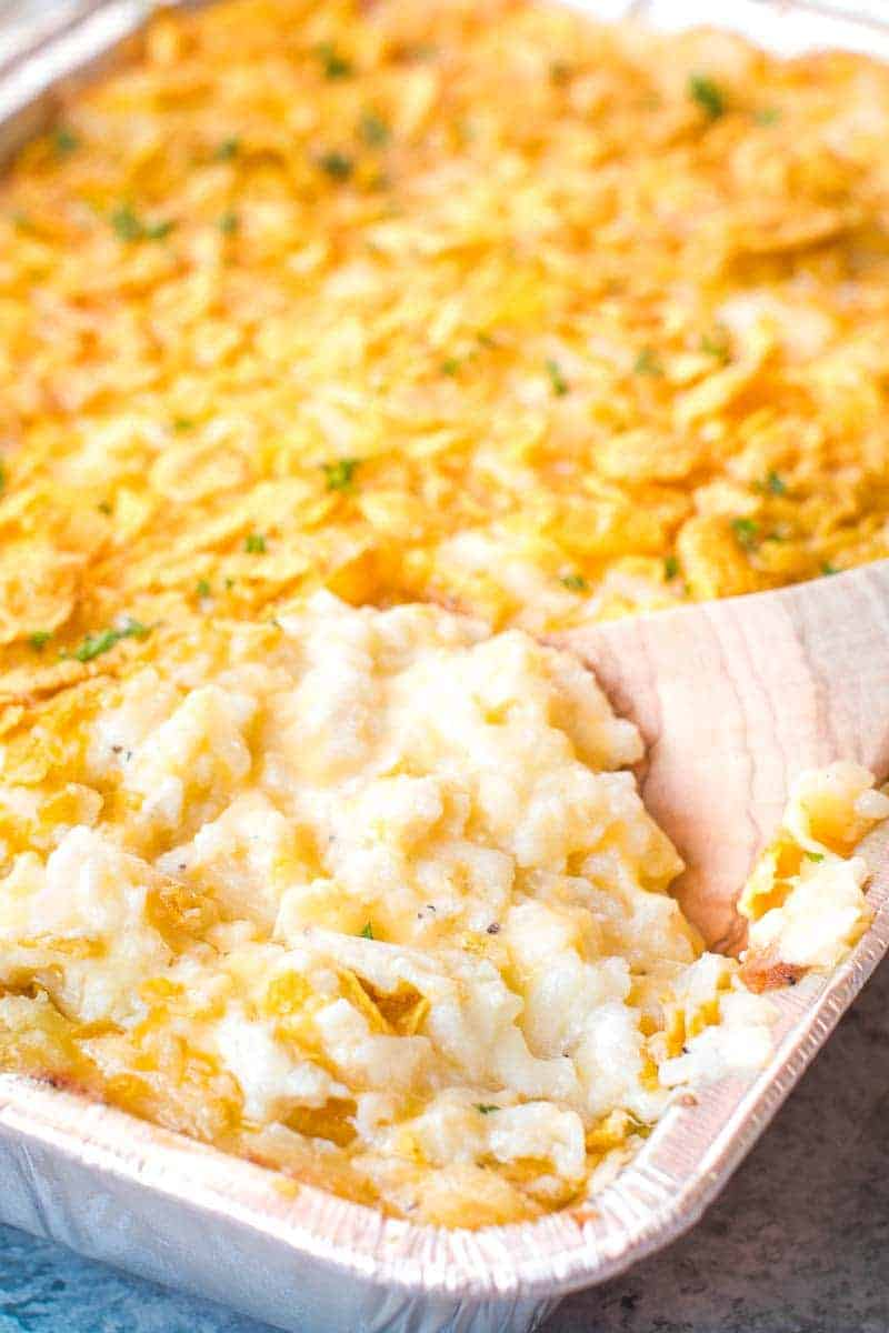 Wooden spoon scooping potato casserole out of foil pan