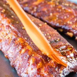 honey garlic smoked ribs being brushed with sauce
