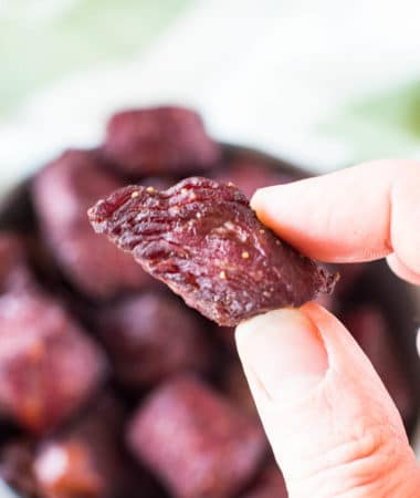 hand holding teriyaki smoked steak bites