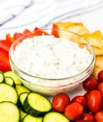 Tzatziki sauce in a glass bowl surrounded by vegetables