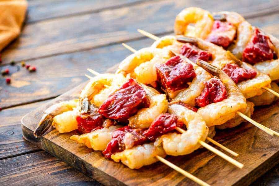 Raw Steak and Shrimp Kabobs on wood cutting board