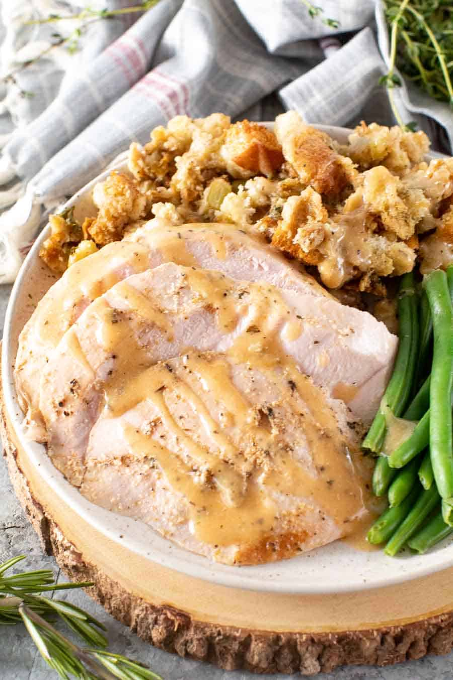 Sliced smoked turkey breasts, smoked stuffing, and green beans on a plate