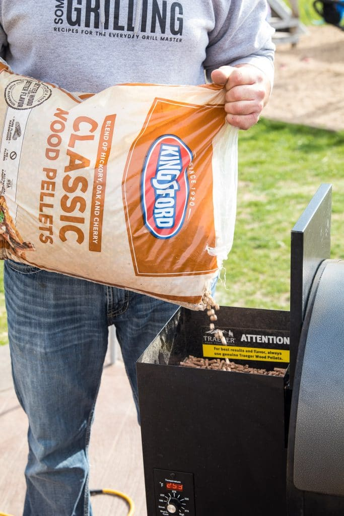 Man pouring Kingsford Classic Wood Pellets into hopper of smoker