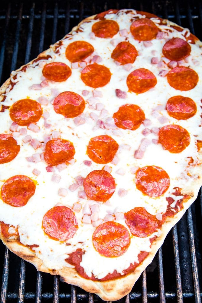 Picture of a pizza on grill grates cooking topped with cheese, diced ham and pepperoni.