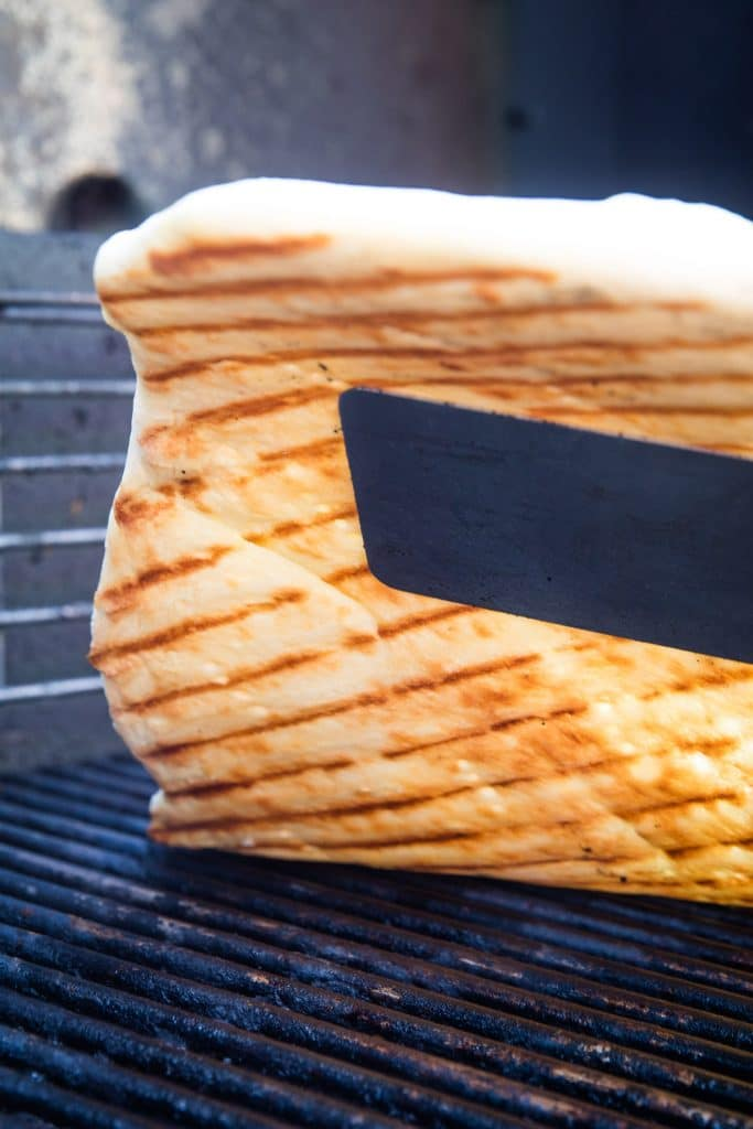 Spatula lifting pizza crust off grill grates to show grill marks on it.