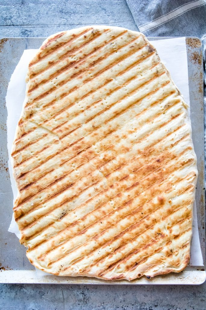 Grilled pizza crust with grill grate marks on pizza pan.