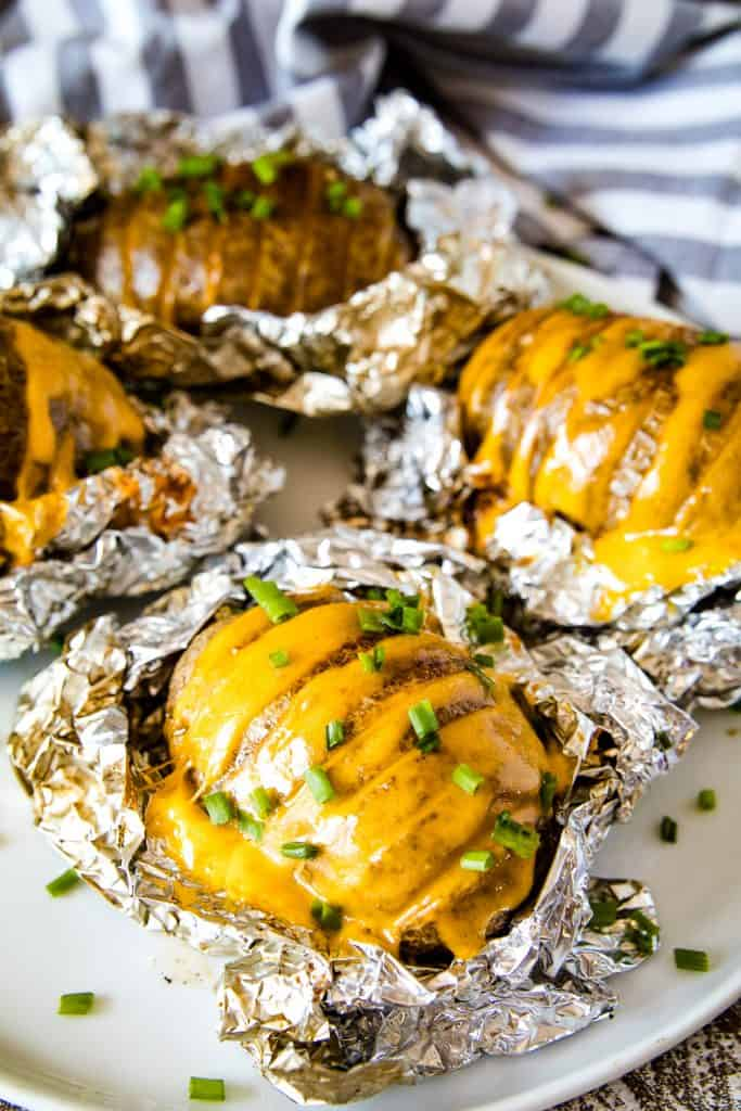 Smoked Hasselback Potatoes stuffed wtih cheese and topped with chopped chives laying on foil that and on a plate.