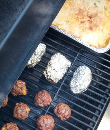 Overhead image of meatballs, foil wrapped potatoes and cake on smoker