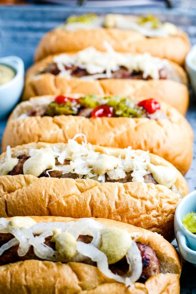 Close up image of five beer brats on buns iwth toppings like mustard, onions, ketuchup and more.