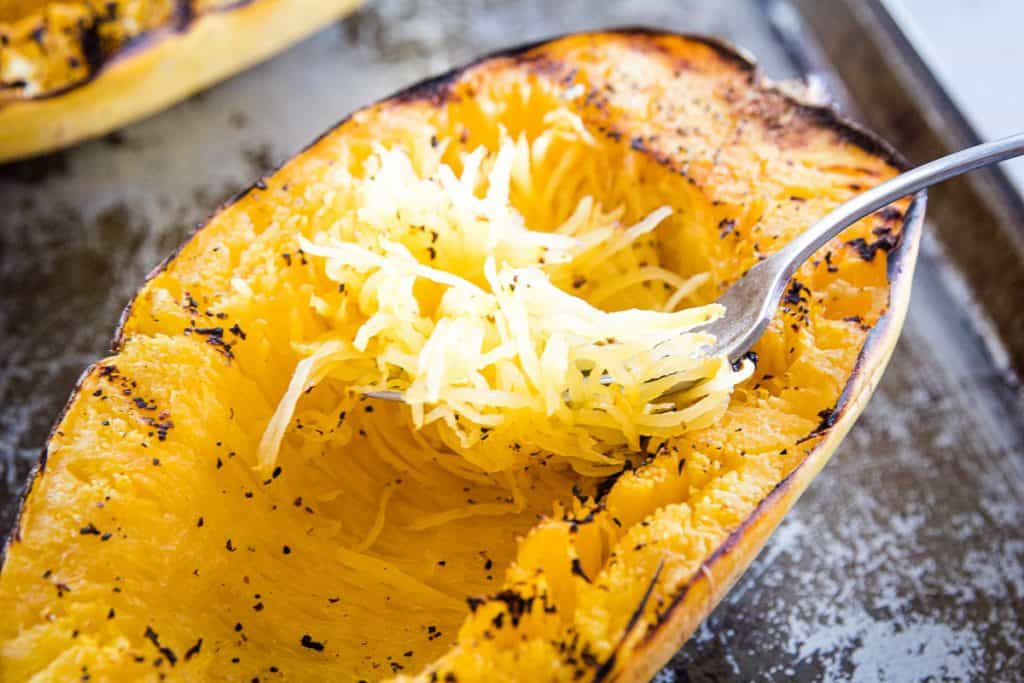 Fork scooping spaghetti squash out of it
