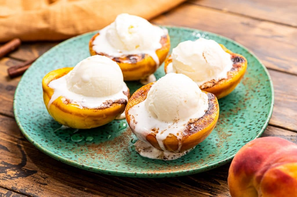 Green plate with grilled peaches topped with ice cream on it.