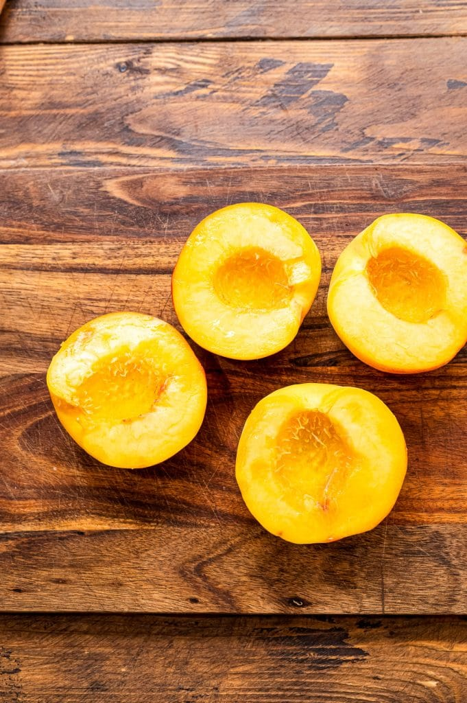 Peaches cut in half laying on wooden background.