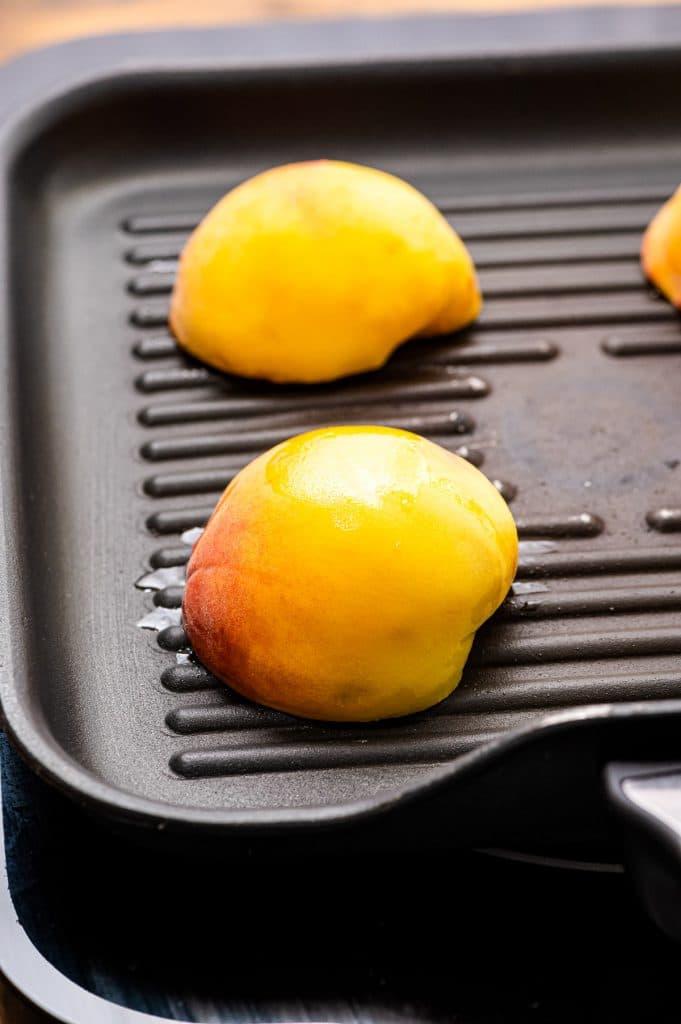 Peach halves face down on grill pan