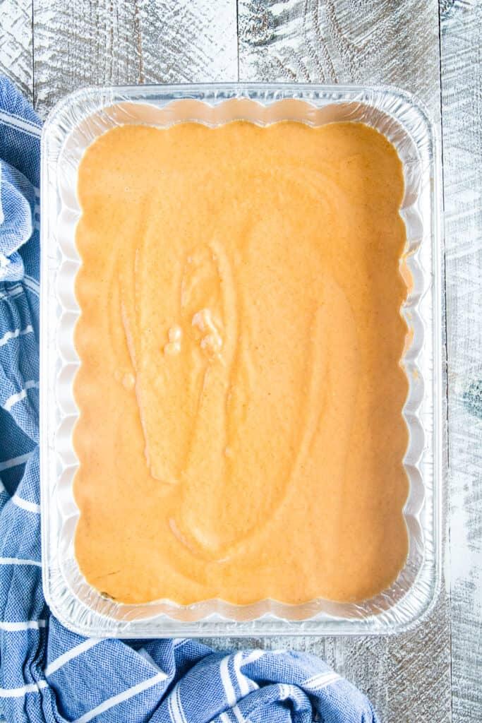 Pumpkin Dump Cake batter in disposable aluminum pan