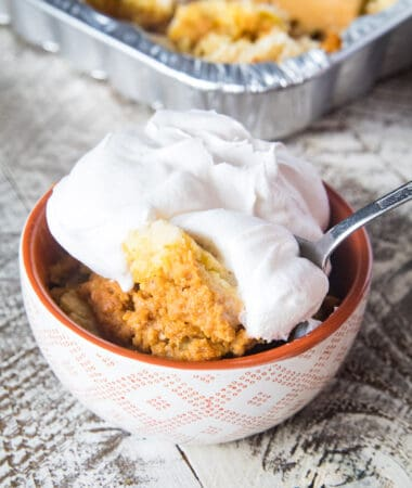 Smoked Pumpkin Dump Cake in bowl topped with cool whip