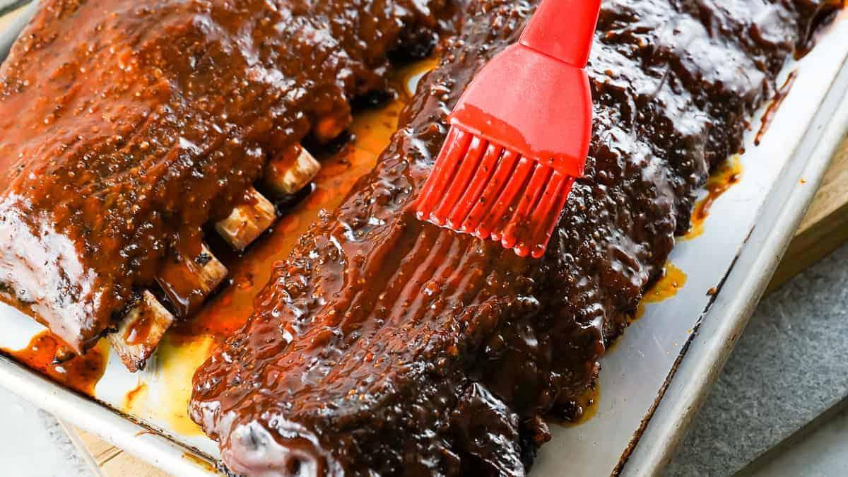 Basting brush applying bbq sauce to ribs