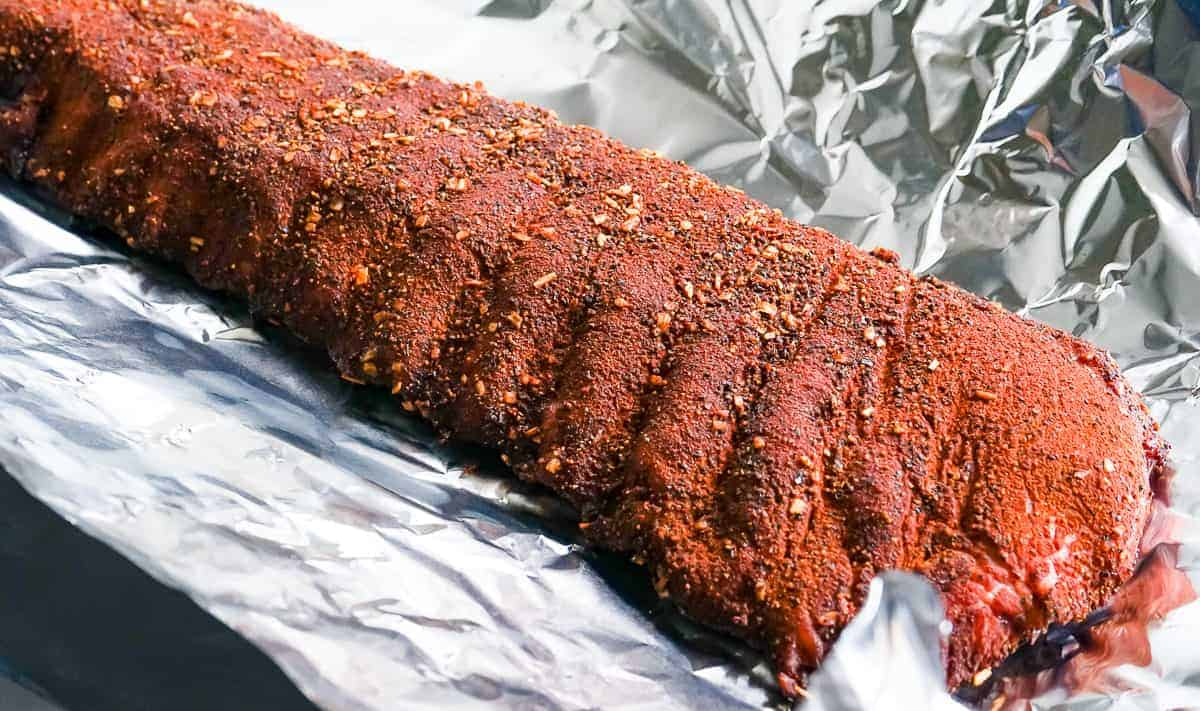 Baby back ribs being wrapped in foil