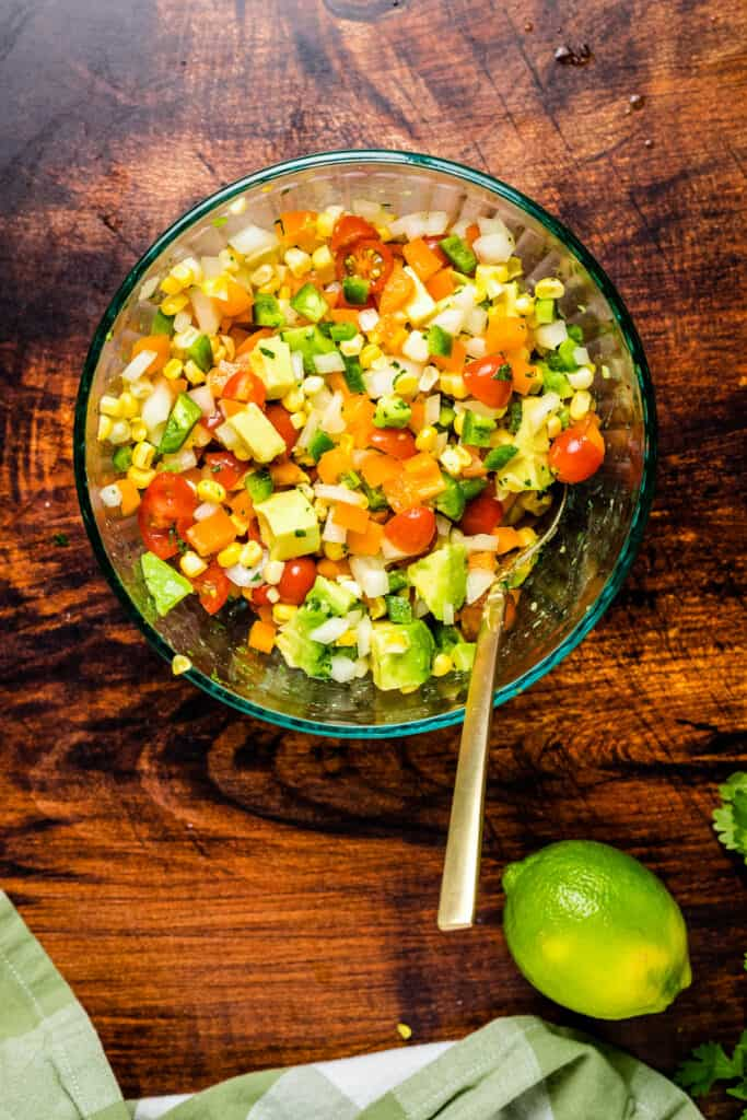 Corn Salsa mixed up in a glass bowl with wooden spoon
