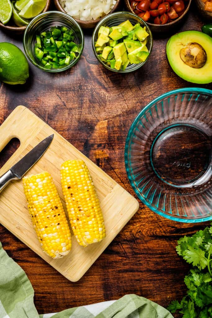 Grilled corn on the cob on cutting board