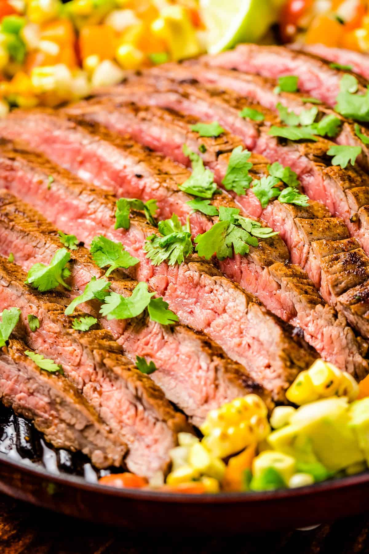 Sliced Grilled Flank Steak topped with chopped parsley and corn salsa
