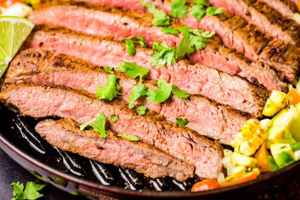 Close up image of sliced flank steak topped with chopped parsley